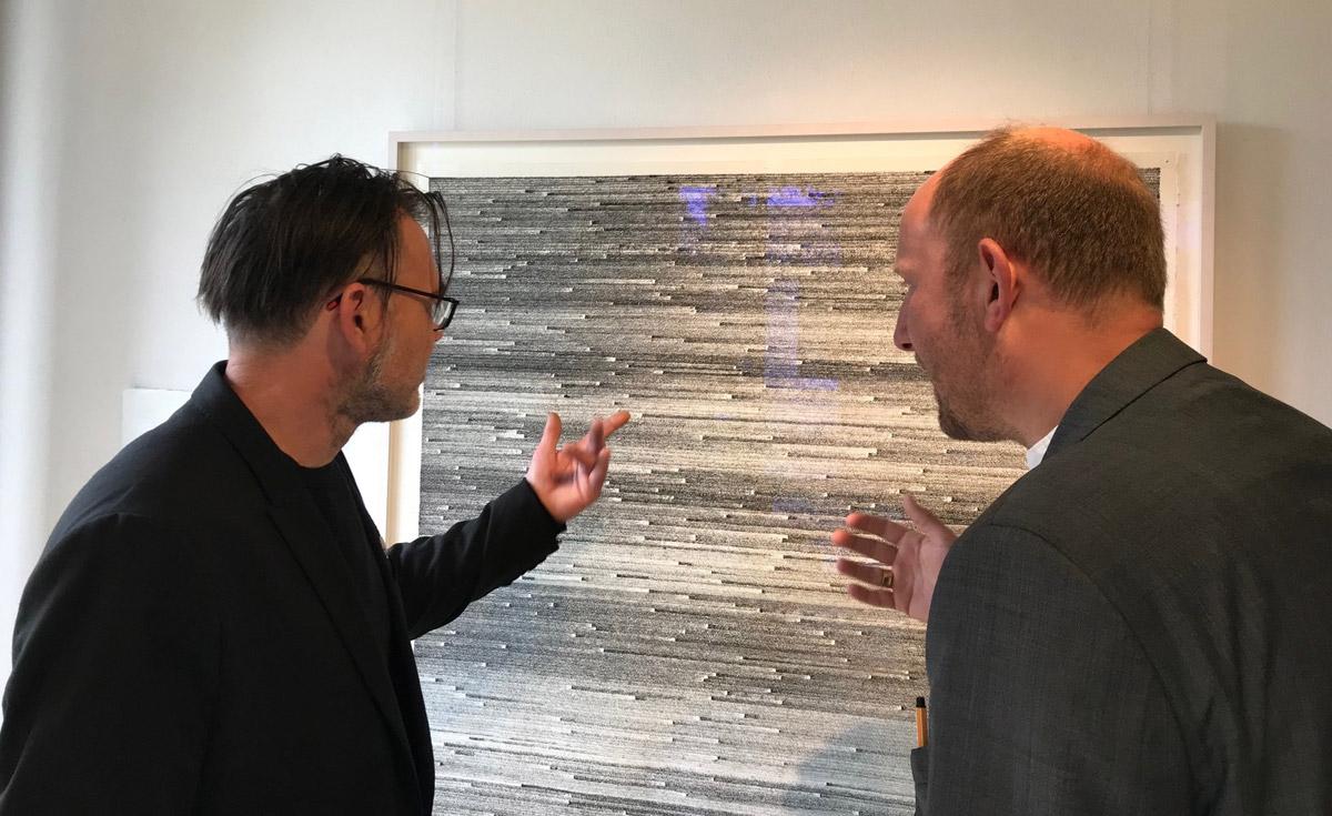 Künstler John Schmitz mit 2. Vorsitzenden Volker Seitz diskutierend vor einem Werk